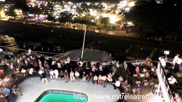 Blick vom obersten Deck auf das Pooldeck von MS Albatros und den Hafen von Papeete bei Nacht