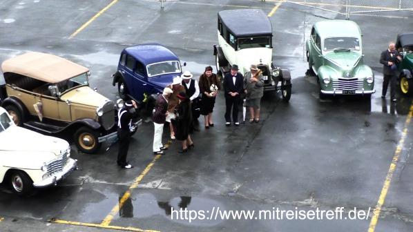 5 Oldtimer mit Personen vor MS Albatros beim Abschied
