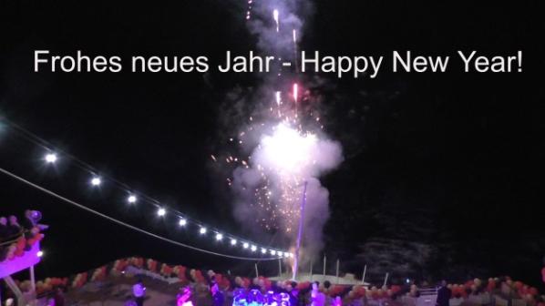 """Blick von oben auf das Pooldeck mit Feuerwerk mit Beschriftung """"Frohes neues Jahr - Happy New Year"""""""