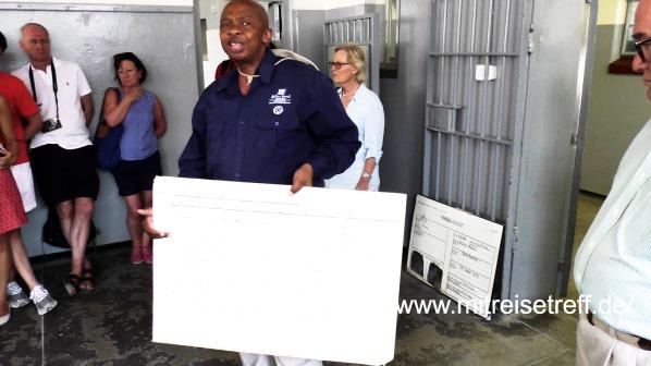 Afrikanischer Führer mit Schautafel in einer Gefängniszelle auf Robben Island