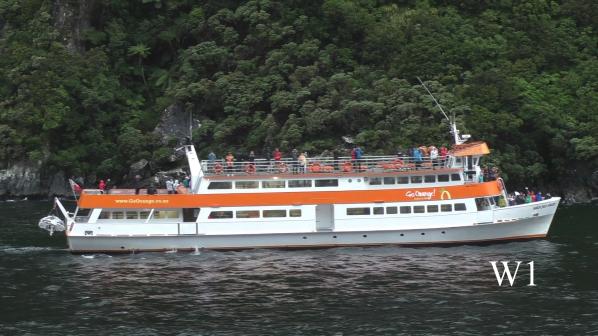 Ausflugsschiff an einem Felsen im Sound