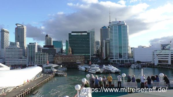 Begeisterte Gäste auf dem Pooldeck von MS Albatros mit Blick auf die Skyline von Auckland