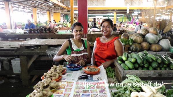 2 freundliche und strahlende Verkäuferinnen am Gemüsestand in der Markthalle