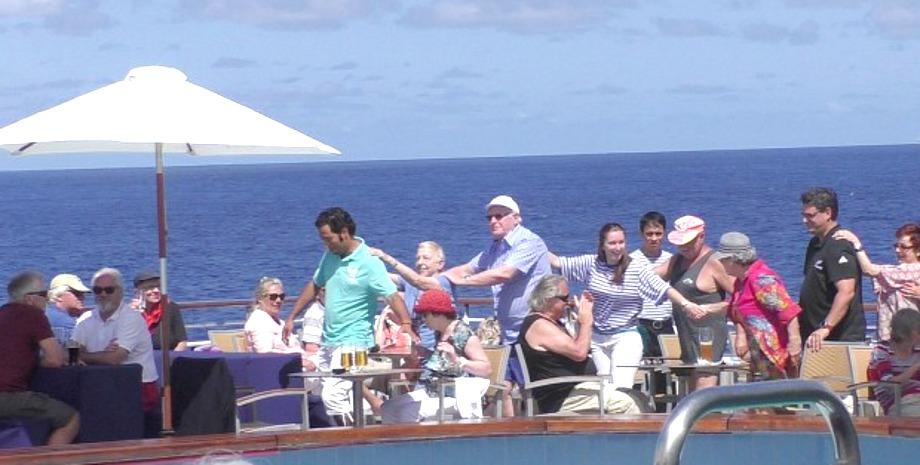 Fröhliche Menschen mit Polonaise auf dem Pooldeck von MS Albatros in der Südsee