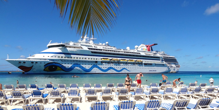 Traumhafter Blick vom Strand Grand Turk Island mit entspannten Menschen und Liegestühlen auf die AIDAvita