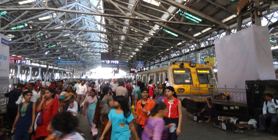 Im Bahnhof vom Mumbai mit Zug und indischen Fahrgästen